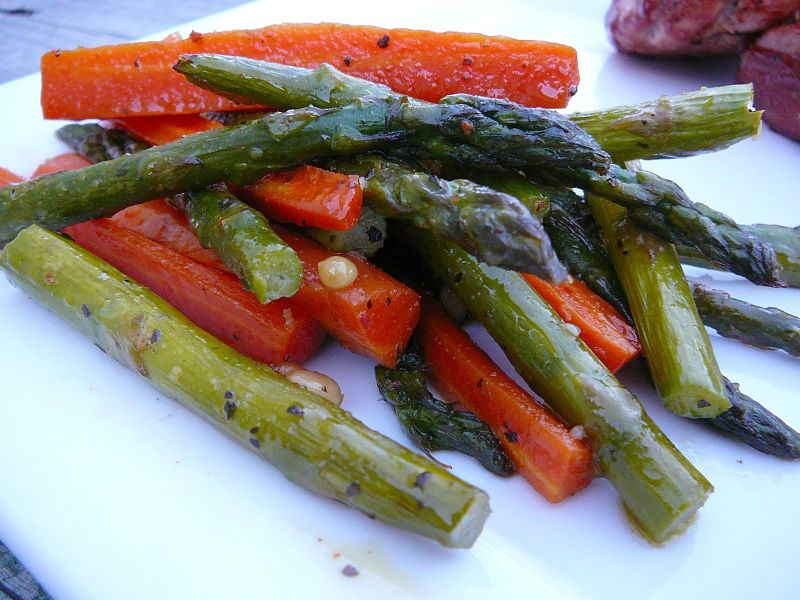 Grilled or barbecued asparagus is a delightful side dish accompanied by bell pepper strips